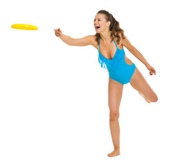 Happy young woman in swimsuit throwing flying disc