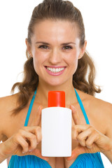 Smiling woman in swimsuit showing bottle of sun screen creme
