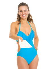 Smiling young woman in swimsuit giving air tickets
