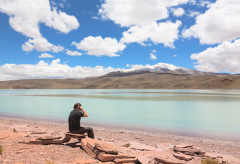 Man sitting on the shore of lagoon Celeste, Bolivia