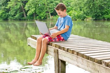 Lachender Jugendlicher mit Notebook am idyllischen Teich