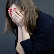 Frau versteckt ihr Gesicht in Händen