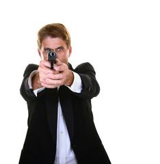 Handsome man in a tuxedo pointing a handgun