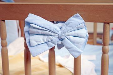 Babybettchen mit blauer Schleife