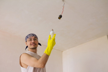 Electrician fixing ceiling light
