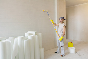 Young man with painting roller painting wallpaper