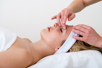 Masseuse massaging a woman eyebrow area.