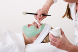 Beautician retouching a blond woman thalasso facial mask.