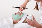 Beautician retouching a blond woman thalasso facial mask. poster