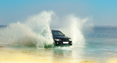 Speed car  through the shallow water on a flat beach