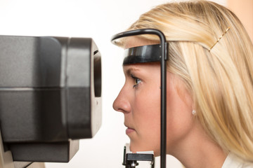 Patientin eines Optikers schaut durch Autorefraktometer