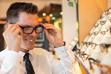 Kunde im Laden eines Optikers probiert Brille