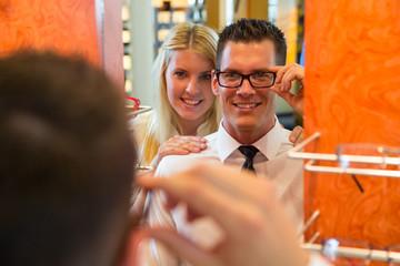 Pärchen in Optiker Laden probiert Brillen