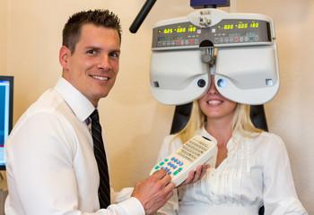 Optiker und Patientin mit einem Phoropter