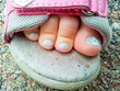 Pedicure on child's toes in sandal