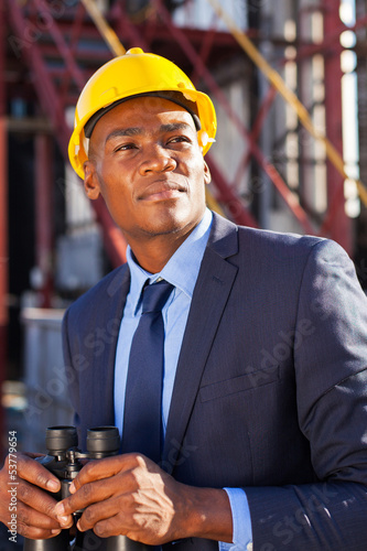 afro american petrochemical businessman with binoculars