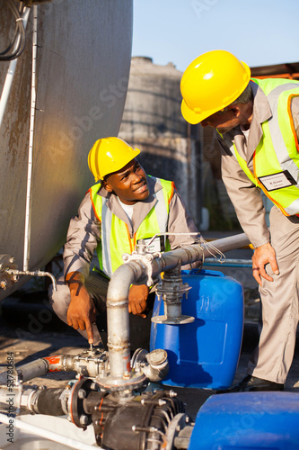 petrochemical wokers inspecting pressure valves on fuel tank
