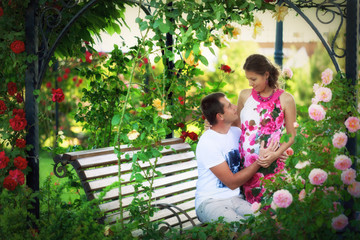 Young couple among the flowers of roses