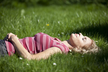 A mid adult woman laying in the grass in summertime