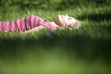 A mid adult woman laying in the grass in summertime, smiling