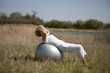 A mature woman exercising on an exercise ball