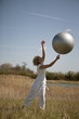 A mature woman catching an exercise ball