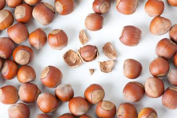 peeled hazelnut among unpeeled, isolated on white background