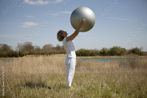 A mature woman holding an exercise ball