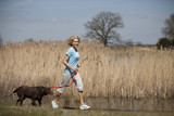 A mature woman jogging in the countryside with her dog