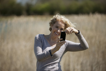 A mature woman taking a photo with a smartphone