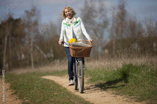 A mature woman cycling along a country path