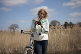 A mature woman out cycling holding a camera