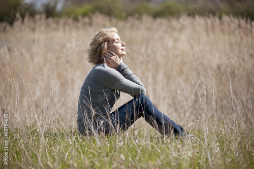A mature woman sitting on the grass, enjoying the sunshine