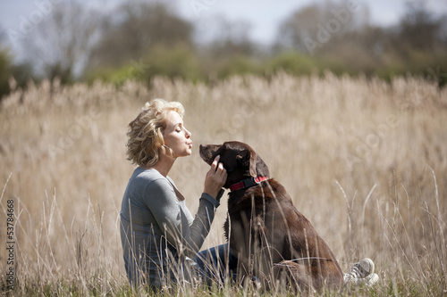 A mature woman sitting on the grass with her dog