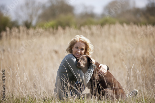 A mature woman sitting on the grass hugging her dog