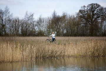 A mature woman pushing a bicycle next to a lake