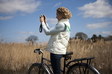 A mid adult woman taking a photograph whilst out cycling