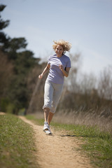 A mature woman running along a country path