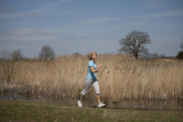 A mature woman power walking in the countryside