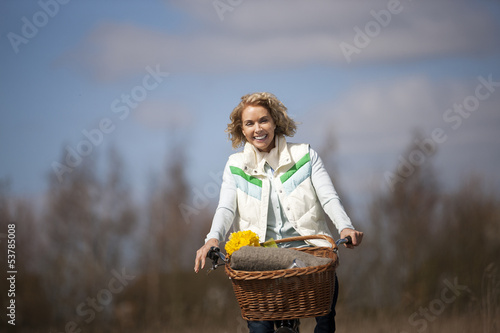 A mid adult woman cycling along a country path, smiling