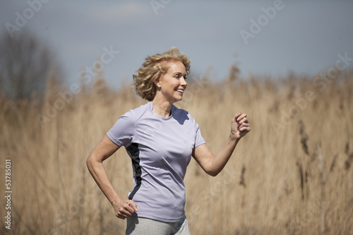 A mature woman running in the countryside