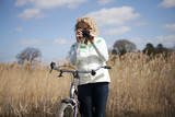 A mature woman taking a photo whilst out cycling