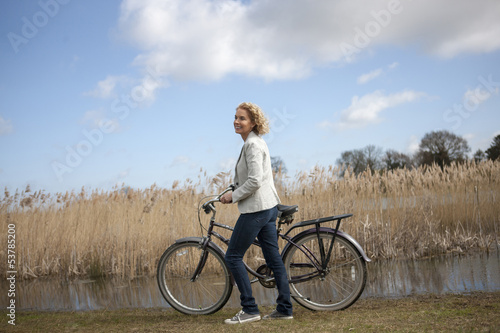 A mid adult woman pushing a bicycle next to a lake