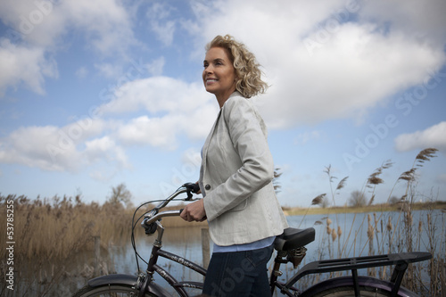 A mature woman standing beside a lake with a bicycle