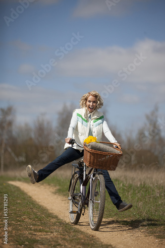 A woman cycling along a country path, legs outstretched