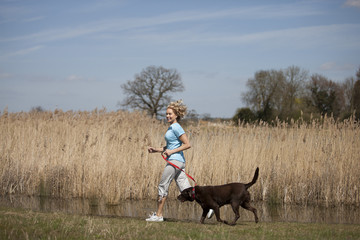 A mid adult woman jogging in the countryside with her dog