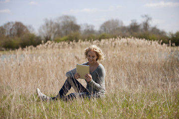 A  woman sitting on the grass, looking at a digital tablet