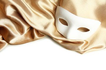 White mask and golden silk fabric, isolated on white