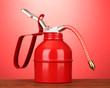 Oil can on red background