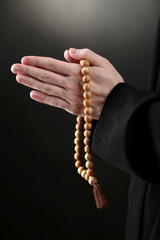 Priest holding rosary, on black background